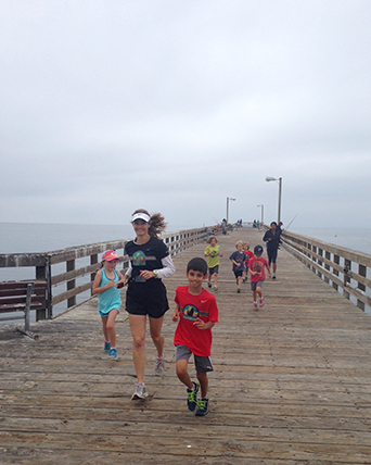 Photo of Coach Becky running with Coyotes on Goleta Beach pier