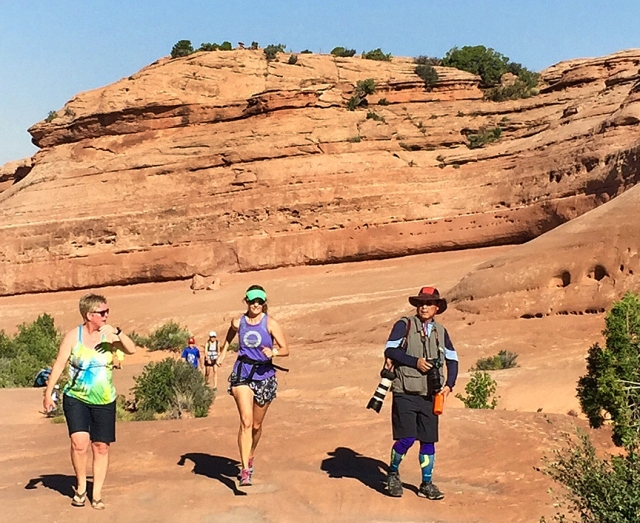 Photo of Becky Aaronson running up to Delicate Arch