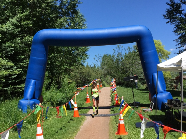 Photo of Patty Bryant crossing the finish line of the Aspen Backcountry Marathon